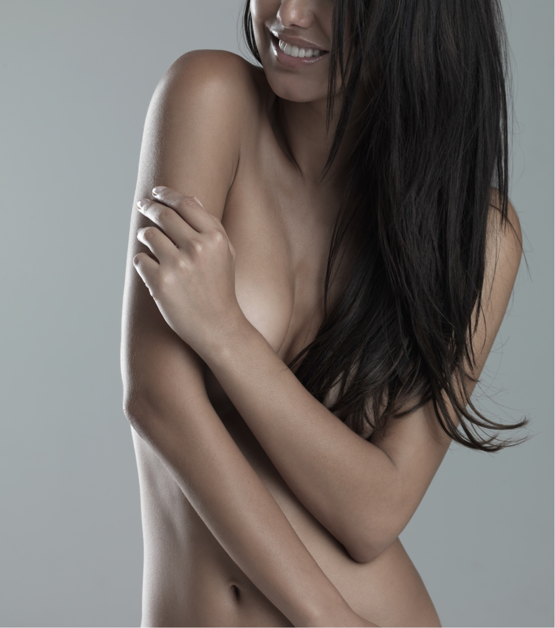 woman smiling covering breasts